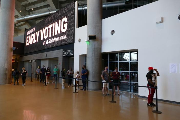 A short line of voters queues up during the first week of early voting to check in at the State Farm Arena precinct, the state's largest polling station.