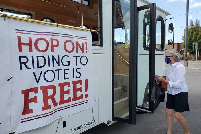 "Rebecca Rolfes boards a trolley, which holds a banner announcing ""riding to vote is free"""