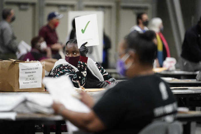 An official holds up a green check mark sign as they sort ballots during an audit at the Georgia World Congress Center on Saturday, Nov. 14, 2020, in Atlanta.