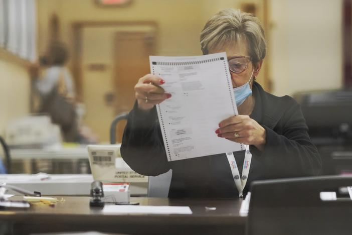 poll worker inspects absentee ballot