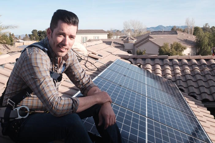 """Power Trip"" director Jonathan Scott takes a break from installing solar panels on a rooftop."