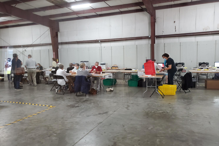 Ballots are counted at a series of tables in a large room in Chatham county.