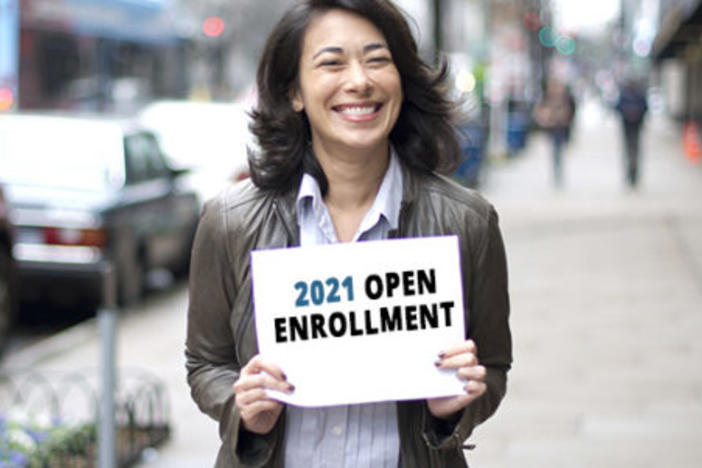 Woman holding open enrollment sign