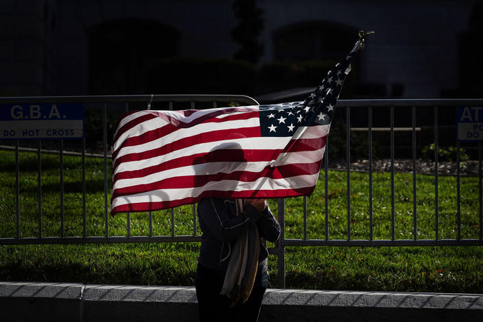 "A woman holding an American flag attends a ""stop the steal"" rally at the Georgia State Capitol."