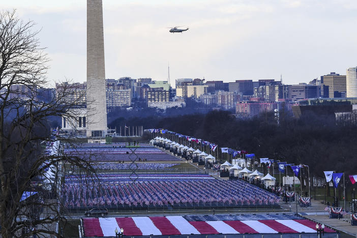 A helicopter carrying the president flies over the national mall where the inauguration is being set up.