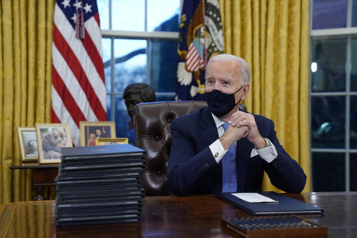 President Joe Biden sits in the oval office next to a stack of executive orders.