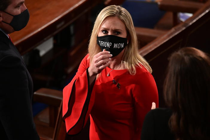 "In this Sunday, Jan. 3, 2021, file photo, Rep. Marjorie Taylor Greene, R-Ga., wears a ""Trump Won"" face mask as she arrives on the floor of the House to take her oath of office on opening day of the 117th Congress at the U.S. Capitol in Washington."