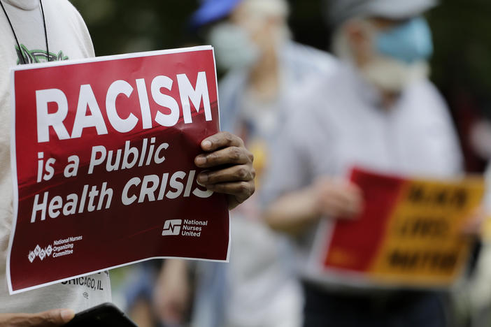 "A person holds a sign that says. ""Racism is a public health crisis."""
