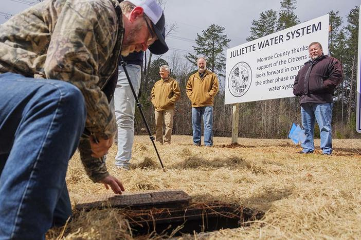 From left, Monroe County Commissioner John Ambrose, Commission Chair Greg Tapley and Monroe County resident Charles Grizzard watch as a worker turns on the water service to Grizzard's house Tuesday. Grizzard was the first resident to get city water in a project inspired by worries about coal ash at Georgia Power's Plant Scherer.