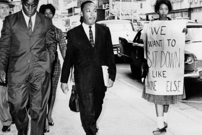 In this Oct. 19, 1960 file photo, Dr. Martin Luther King Jr. under arrest by Atlanta Police Captain R.E. Little, left rear, passes through a picket line outside Rich's Department Store, in atlanta.