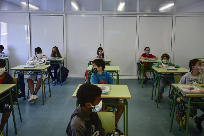 Students wearing masks sit at rows of desks in a classroom.