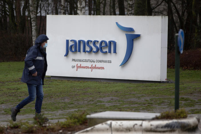 A man walks by a sign outside Johnson & Johnson subsidiary, Janssen Pharmaceutical, in Geel, Belgium, Wednesday, Feb. 3, 2021.