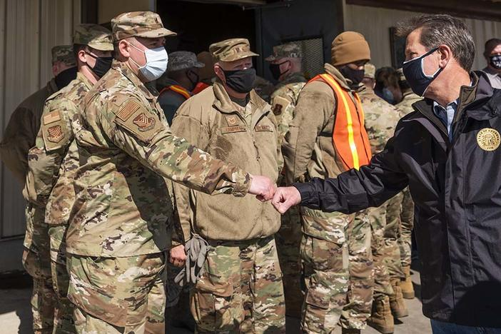 Governor Brian Kemp greets Georgia Air National Guard members staffing the mass vaccination site at the state farmers market in Macon.