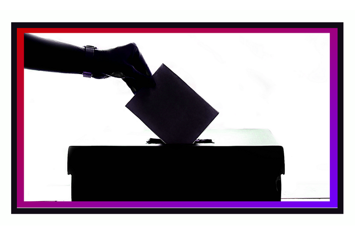 An illustration of a hand dropping a ballot into a ballot box.