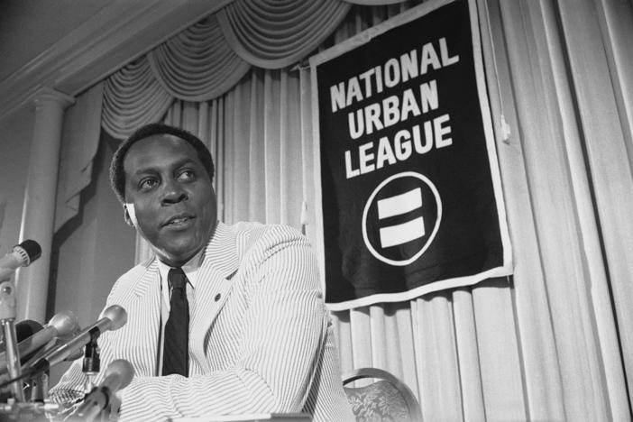 A black and white photo of Vernon Jordan sitting at some microphones during a press conference with the National Urban League.
