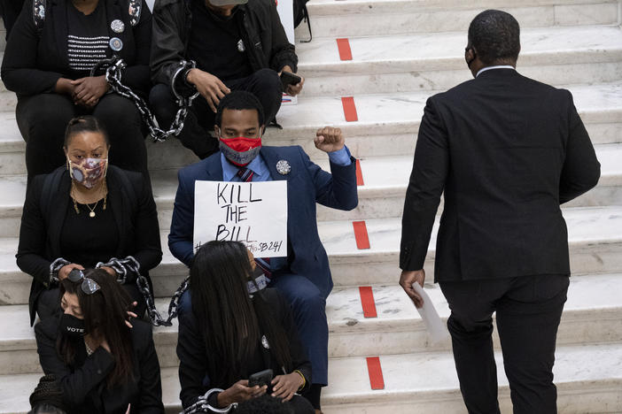 Protesters opposed to changes in Georgia's voting laws sit on the steps inside the State Capitol in Atlanta, Ga., as the Legislature meets Monday, March 8, 2021, in Atlanta.