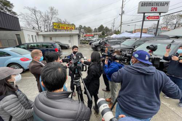 Atlanta-based CNN correspondent Natasha Chen (center, black coat) reports as Georgia Rep. Sam Park makes remarks at one of the sites of the March 16 mass shooting at three Asian-owned massage businesses.