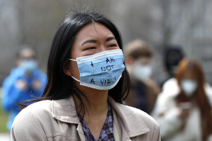 "An Asian woman wearing a mask that says ""I am not a virus."""