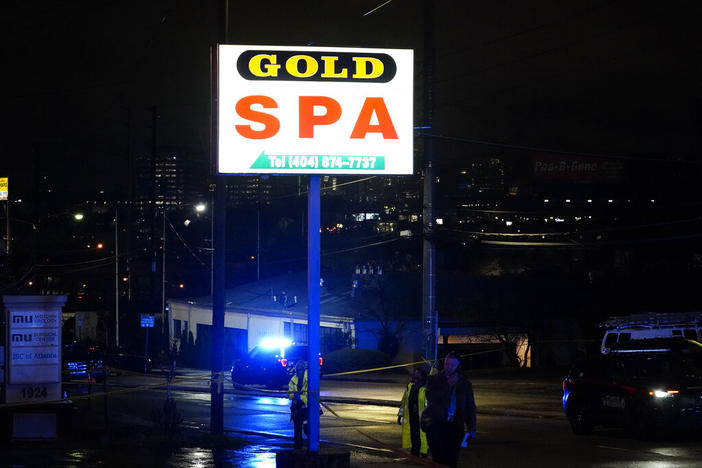 Officials talk on the phone in front of Gold Spa after a shooting on Tuesday, March 16, 2021, in Atlanta. Shootings at two massage parlors in Atlanta and one in the suburbs left multiple people dead, many of them women of Asian descent, authorities said. A 21-year-old man suspected in the shootings was taken into custody in southwest Georgia hours later after a manhunt, police said.