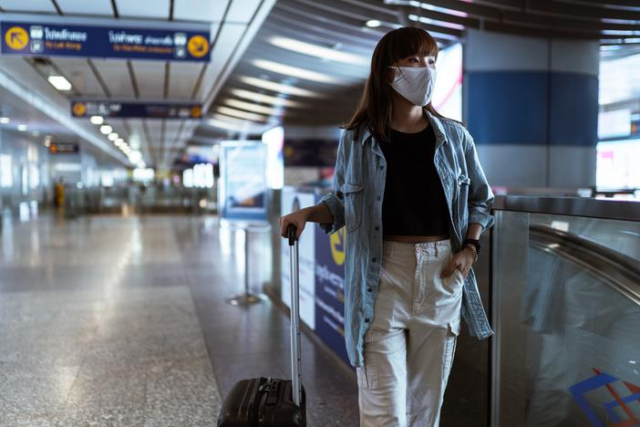 A woman in an airport wearing a face mask and holding luggage.