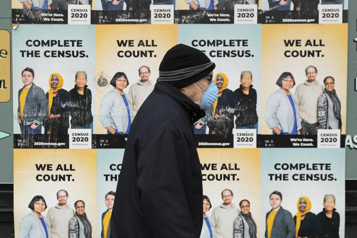 In this April 1, 2020, file photo, a man wearing a mask walks past posters encouraging participation in the 2020 Census in Seattle's Capitol Hill neighborhood. A delay in census data is scrambling plans in some states to redraw districts for the U.S. House and state legislatures. The Census Bureau has said redistricting data that was supposed to be provided to states by the end of March won't be ready until August or September. (AP Photo/Ted S. Warren, File)