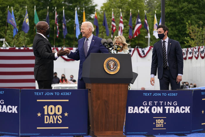 President Joe Biden greets Sen. Raphael Warnock, D-Ga., left, as first lady Jill Biden and Sen. Jon Ossoff, D-Ga., watch, during a rally at Infinite Energy Center, to mark his 100th day in office, Thursday, April 29, 2021, in Duluth, Ga.