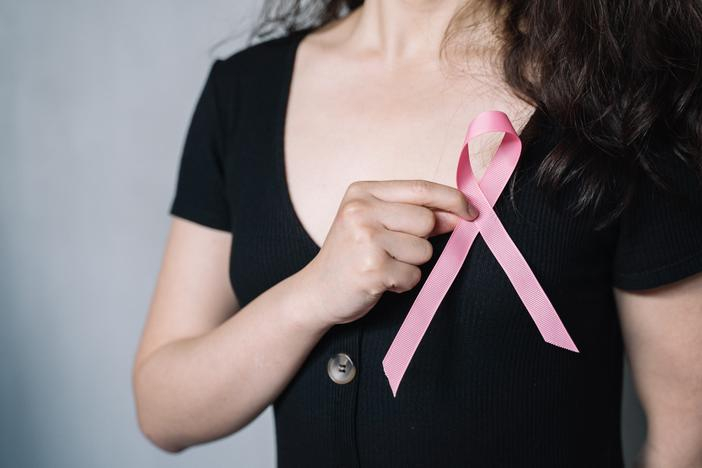 Woman holds pink ribbon to her chest