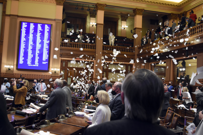 Lawmakers throw torn papers into the air at the end of the 2021 legislative session in the General Assembly just after midnight on April 1, 2021.