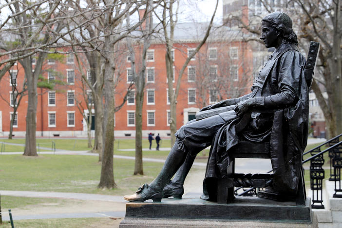 A statue of John Harvard, namesake of the university, overlooks the campus earlier this year. Harvard University joined the Massachusetts Institute of Technology in suing the federal government over its policies on international students Wednesday.