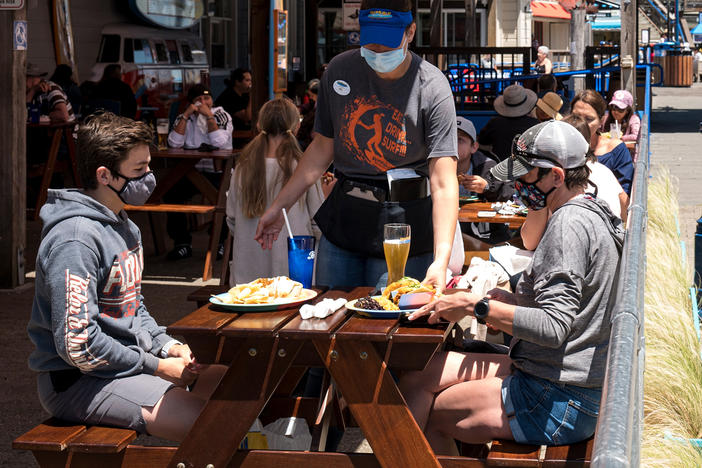 Patrons wear masks as they sit on the outdoor patio of a restaurant on Pier 39 at Fisherman's Wharf in San Francisco. California is among more than 20 states that require face masks to help combat the spread of the coronavirus.