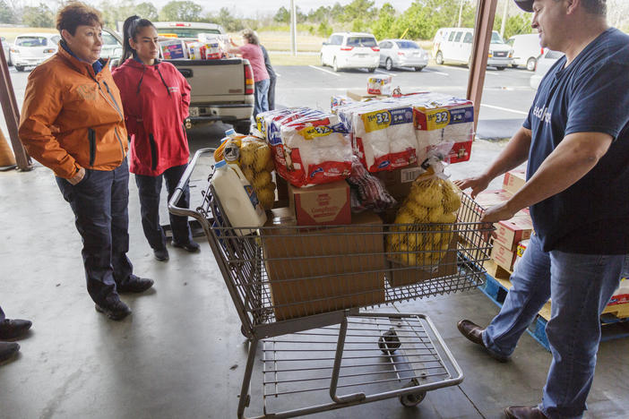 Douglas Griner, right, partner services director of the Second Harvest of South Georgia food bank in Valdosta, loads up food for three TSA workers Thursday morning.