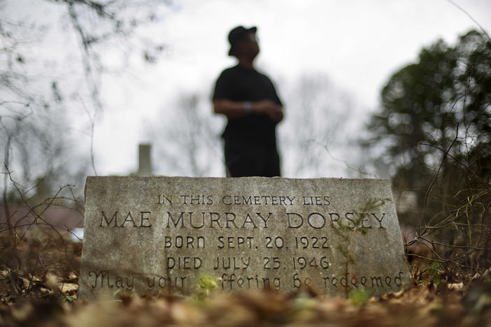Tyrone Brooks, a veteran civil rights activist, stands behind the tombstone of Mae Murray Dorsey who was killed in a 1946 lynching by a white mob in Monroe, Ga., Thursday, Feb. 22, 2018.