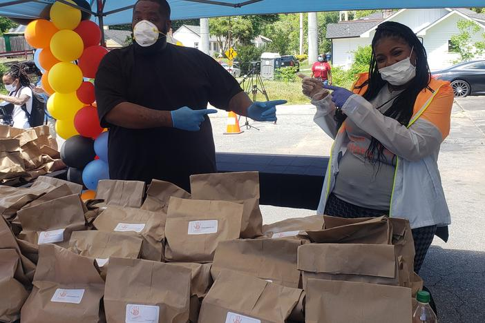 "Michael ""Killer Mike"" Render hands out meals with PAWkids founder Latonya Gates at Bankhead Seafood Market."