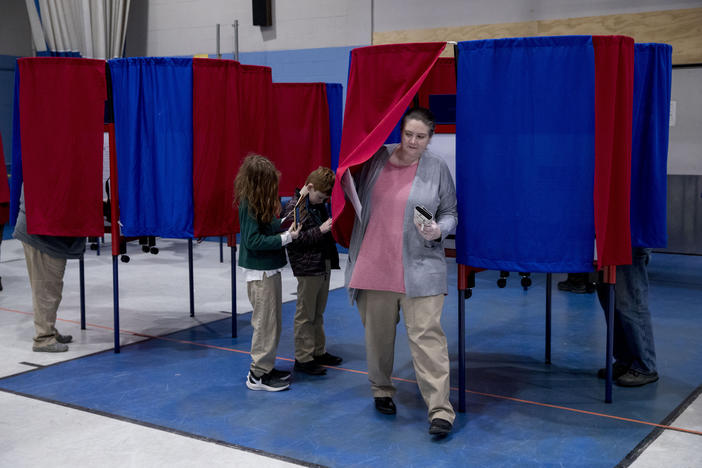 Samantha Murch, center, accompanied by her two boys Alexander, 8, and Jacob, 11, left, steps out of the voting booth for the New Hampshire primary at Bishop O'Neill Youth Center, Tuesday, Feb. 11, 2020, in Manchester, N.H.