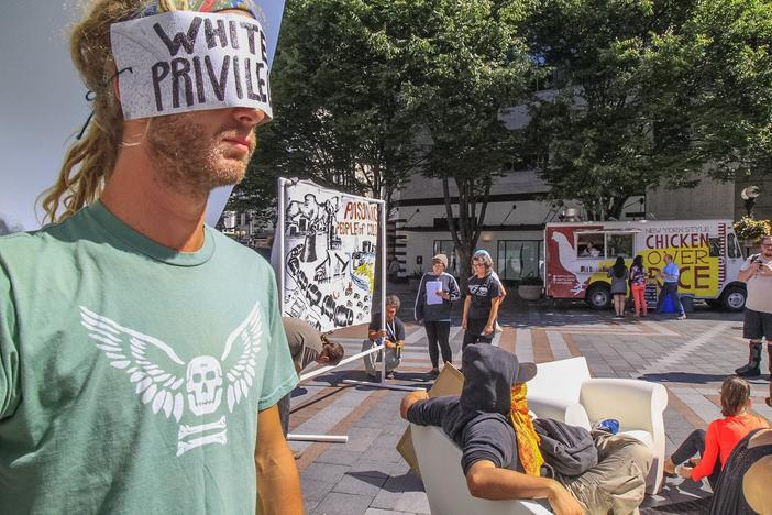 "In Seattle, WA people are invited to participate in a public interactive art installation to expose racism as the""elephant in the room""."