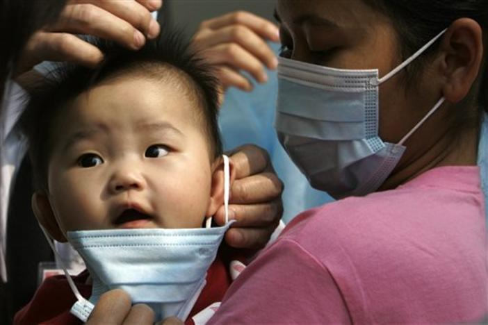 A baby wearing a mask as a preventative measure against a flu outbreak when entering a hospital in Hong Kong Sunday March 16, 2008.