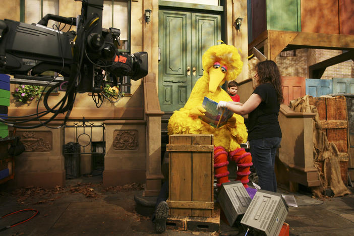 "Michelle Hickey, a muppet wrangler, helps Big Bird hold a book during a rehearsal of ""Sesame Street"" in New York."