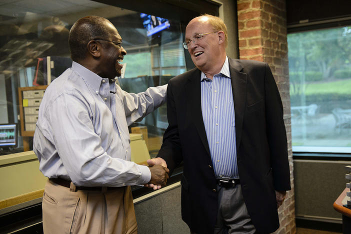 Former Republican Presidential candidate Herman Cain shakes hands with news talk radio host Neal Boortz after he was announced as Boortz's replacement following Boortz's retirement announcement during his morning show at WSB in Atlanta in 2012.