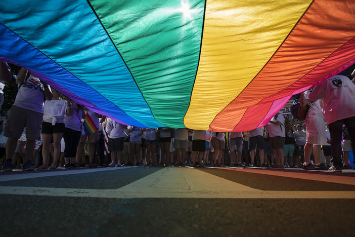 Marchers unfurl a huge rainbow flag as they prepare to march in the Equality March for Unity and Pride in Washington, Sunday, June 11, 2017.