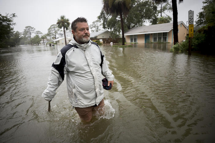 Joey Spalding walks back to his truck down the street where he lives, Monday, Sept., 11, 2017, on Tybee Island, Ga. He said the Tropical Storm Irma brought three feet of storm surge into his living room.
