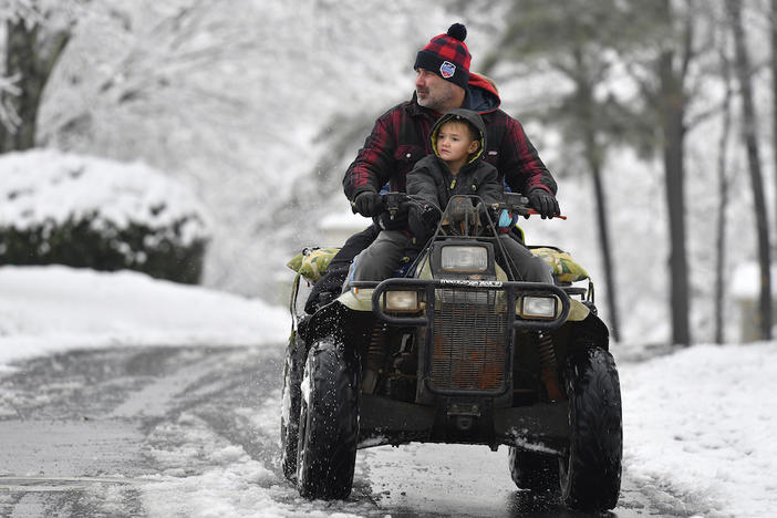 Jimmy Squibb and his son Nash ride an all-terrain vehicle as they survey their neighborhood after a heavy snow fall, Saturday, Dec. 9, 2017, in Kennesaw, Ga.