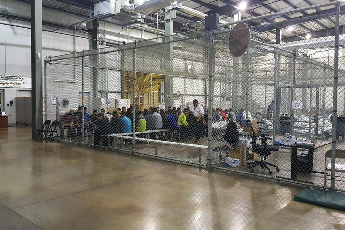 In this photo provided by U.S. Customs and Border Protection, people who've been taken into custody related to cases of illegal entry into the United States, sit in one of the cages at a facility in McAllen, Texas, Sunday, June 17, 2018.