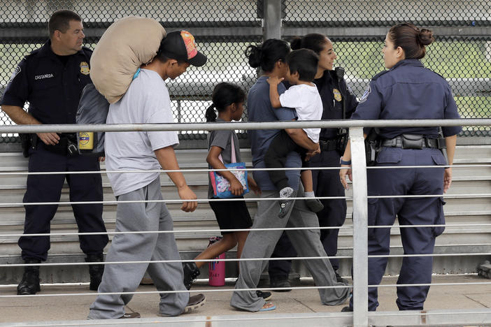Ever Castillo, left, and his family, immigrants from Honduras, are escorted back across the border by U.S. Customs and Border Patrol agents Thursday, June 21, 2018, in Hildalgo, Texas.