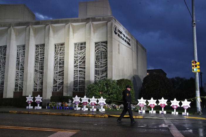 A Pittsburgh Police officer walks past the Tree of Life Synagogue and a memorial of flowers and stars in Pittsburgh in remembrance of those killed and injured when a shooter opened fire during services Saturday at the synagogue.