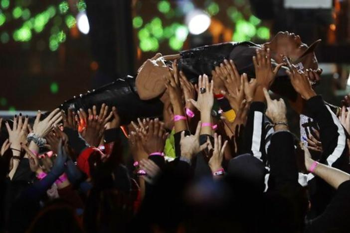 Travis Scott is carried by the crowd during halftime show of the NFL Super Bowl 53 football game between the Los Angeles Rams and the New England Patriots Sunday, Feb. 3, 2019, in Atlanta.