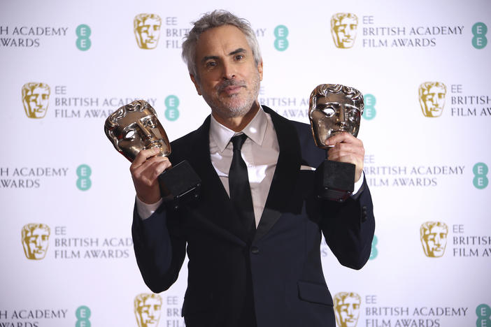 Director Alfonso Cuaron poses for photographers backstage with his Best Film and Best Director award for his film 'Roma' at the BAFTA awards in London, Sunday, Feb. 10, 2019.