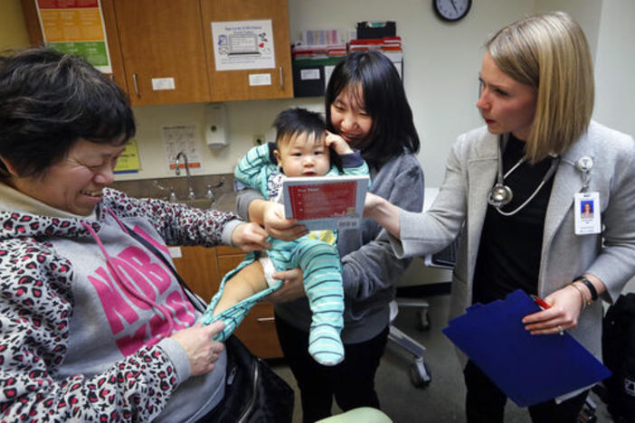 Mother Wenyi Zhang holds 1-year-old Abel Zhang moments after he received a vaccine for measles, mumps, and rubella (MMR), at the International Community Health Services Wednesday, Feb. 13, 2019, in Seattle.