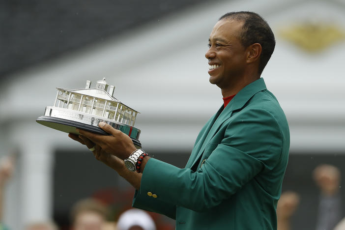 Tiger Woods wears his green jacket holding the winning trophy after the final round for the Masters golf tournament Sunday, April 14, 2019, in Augusta, Ga.