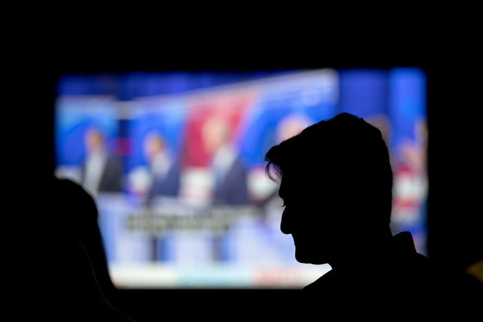 A person watches a broadcast of a Democratic presidential debate at a bar in Atlanta, Thursday, June 27, 2019.