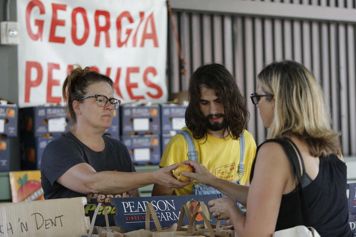 In this photo taken on Tuesday, June 25, 2019, Rebecca Kern, left, and Ryder Seigle, right, sell Pearson Farm peaches and pecans at the Ponce City Farmers Market in Atlanta.